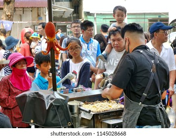 KAOHSIUNG, TAIWAN -- JULY 14, 2018: An outdoor vendor cooks Japanese Takoyaki squid balls during the 2018 Street Art Festival.