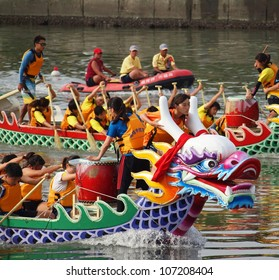 KAOHSIUNG, TAIWAN - JUNE 23: Two unidentified teams of female athletes compete in the 2012 Dragon Boat Races on the Love River on June 23, 2012 in Kaohsiung