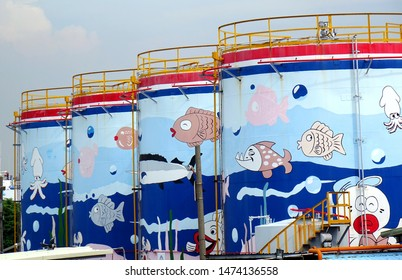 KAOHSIUNG, TAIWAN -- JUNE 27, 2019: Large fuel storage tanks are painted with colorful ocean scenes.