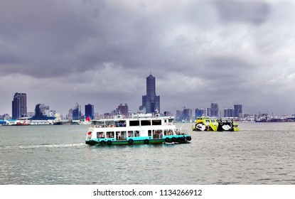 KAOHSIUNG, TAIWAN -- JUNE 30, 2018: The old and the new cross-harbor ferries pass by each other under a gloomy dark sky.