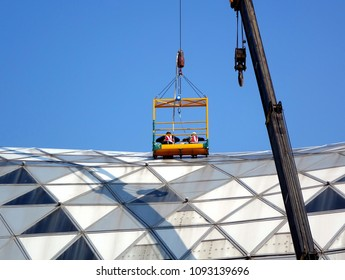 KAOHSIUNG, TAIWAN -- MAY 13, 2018: Workers suspended by a crane inspect the roof of the Kaohsiung Exhibition Center.