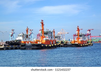 KAOHSIUNG, TAIWAN -- MAY 26, 2018: A line of tugboats are anchored at the Kaohsiung container port in preparation for service.