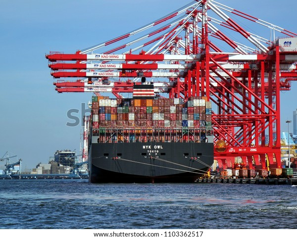 KAOHSIUNG, TAIWAN -- MAY 26, 2018: A large container ship is being loaded in the busy port of Kaohsiung, a major trading hub for Taiwan.