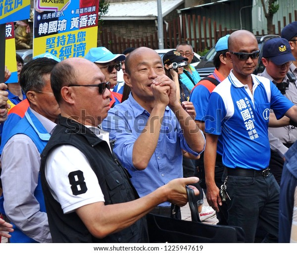 KAOHSIUNG, TAIWAN -- NOVEMBER 10, 2018: KMT Kaohsiung mayor candidate Han Guo-Yun (center, blue shirt), surrounded by security, greets supporters on his arrival at an election rally.