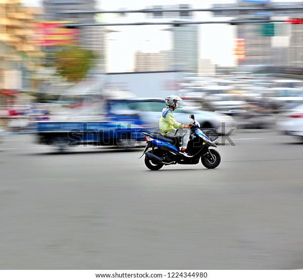 KAOHSIUNG, TAIWAN -- NOVEMBER 3, 2018: Taiwan boasts 15 million registered scooters, the highest motorcycle density in the world. This image features motion blur to show movement and speed.