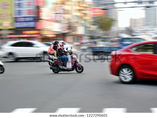 KAOHSIUNG, TAIWAN -- NOVEMBER 3, 2018: Taiwan boasts 15 million registered scooters, the highest motorcycle density in the world. Image features motion blur.