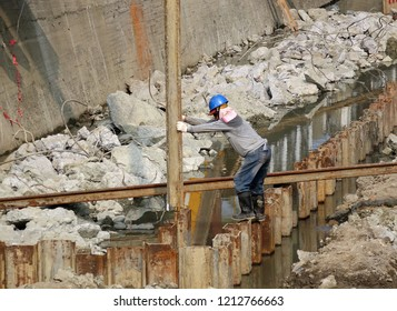 KAOHSIUNG, TAIWAN -- OCTOBER 10, 2018: A construction worker guides the placement of a steel girder to be driven into the ground by a pile driver.