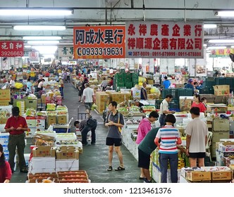 KAOHSIUNG, TAIWAN -- OCTOBER 13, 2018: Wholesale as well as retail shoppers look at fruit at the central fruit and vegetable market in Kaohsiung City.