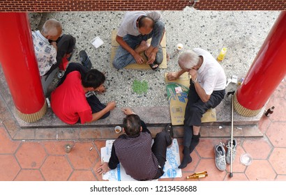 KAOHSIUNG, TAIWAN -- OCTOBER 19, 2018: Four elderly men play checkers under the roof of a local temple.