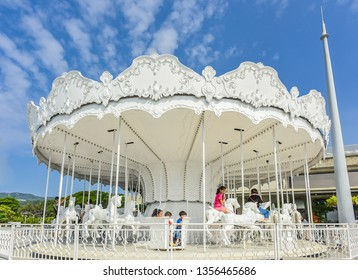 Kaohsiung, Taiwan-December 15, 2018 : White Carousel And The Harbor At The Historical Building of Kaohsiung Port Warehouse No.2 (KW2), Pier 2 Art Center