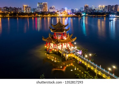 Kaohsiung's famous tourist attractions aerial view, Beautiful decorated traditional Chinese Pagoda with Kaohsiung city in background at night, Wuliting, Kaohsiung, Taiwan.