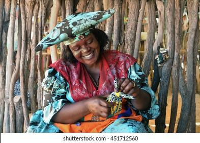 KAOKOLAND, NAMIBIA - FEB 1, 2016: Smiling  Herero Woman in traditional clothes makes a doll. The Herero belonging to the Bantu group, with about 240,000 members alive today.