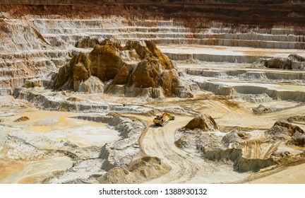 Kaolin quarry with white plaster material and yellow excavator, Vetovo village area, Bulgaria.