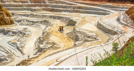 Kaolin quarry with white plaster material and trucks