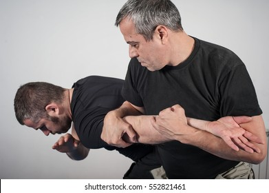 Kapap instructor demonstrates arm bar techniques with his student