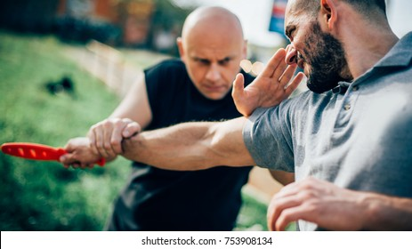 Kapap instructor demonstrates martial arts self defense disarming technique against threat and knife attack. Weapon retention and disarm training. Demonstration with plastic knife