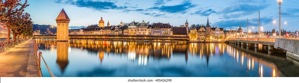 Kapellbrucke Panorama night view Historic Chapel bridge (Famous covered wooden footbridge), Water Tower, Chateau Gutsch, Jesuitenkirche over Reuss river Cityscape old town under Blue Sky, Switzerland