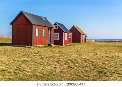 Kapelludden on Oland, Sweden. Red wooden fishing cabins in a row along the coast.