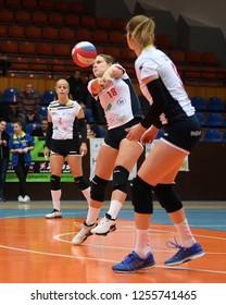 KAPOSVAR, HUNGARY – DECEMBER 2, 2018: Norina Csaszar receives ball at a Hungarian National Championship volleyball game between Kaposvar (white) and Palota VSN (blue) in Sportcsarnok Kaposvar.