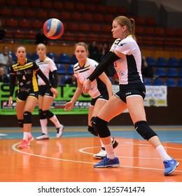 KAPOSVAR, HUNGARY – DECEMBER 2, 2018: Ildiko Szivos receives ball at a Hungarian National Championship volleyball game between Kaposvar (white) and Palota VSN (blue) in Sportcsarnok Kaposvar.