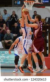 KAPOSVAR, HUNGARY - DECEMBER 22: Gabor Drahos (in white) in action at Hungarian Championship basketball game with Kaposvar (white) vs. Debrecen (claret) on December 22, 2012 in Kaposvar, Hungary.