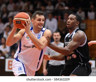 KAPOSVAR, HUNGARY - FEBRUARY 4: Marton Fodor (with ball) in action at Hungarian Championship basketball game with Kaposvar (white) vs. Pecsi VSK (black) on February 4, 2017 in Kaposvar, Hungary.