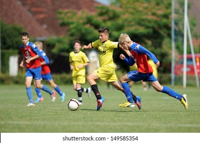 KAPOSVAR, HUNGARY - JULY 20: Unidentified players in action at the IX. Youth Football Festival match Minsk (red) (BLR) vs. Brasov (yellow) (ROM) on July 20, 2013 in Kaposvar, Hungary