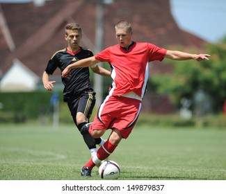 KAPOSVAR, HUNGARY - JULY 20: Unidentified players in action at the IX. Youth Football Festival match Nagybajom (red) (HUN) vs. Liceul Sportiv (black) (MDA) on July 20, 2013 in Kaposvar, Hungary