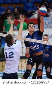 KAPOSVAR, HUNGARY – NOVEMBER 29, 2018: Akos Kalmar (with ball) in action at a Hungarian National Cup volleyball game between Kaposvar (blue) and MAV Elore (white) in Sportcsarnok Kaposvar.