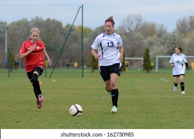 KAPOSVAR, HUNGARY - NOVEMBER 3: Kata Recsei (white 13) in action at Hungarian Championship under 15 women soccer game Rakoczi FC (white) vs Pecsi MFC (red) November 3, 2013 in Kaposvar, Hungary.