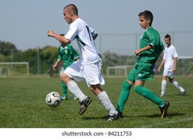 KAPOSVAR, HUNGARY - SEPTEMBER 5: Attila Kovacs (white 11) in action at the Hungarian National Championship under 17 game Kaposvar (white) vs. Nagyatad (green) September 5, 2011 in Kaposvar, Hungary.