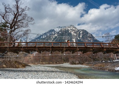The Kappa Suspension Bridge at Kamikochi in the Chubu Sangaku National Park. Beautiful old, wooden suspension bridge with the Hotaka mountains behind