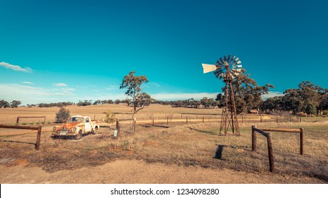 Kapunda, South Australia - June 17, 2017: Rusty Holden FJ Ute and vintage Kookaroo windmill on display near farm entrance from highway