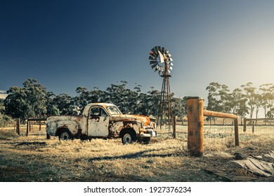 Kapunda, South Australia - June 17, 2017: Abandoned rusty Classic Holden FJ Ute parked next to an old windmill viewed from the road