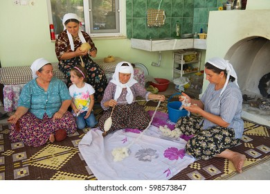 KARACAHISAR, TURKEY - AUGUST 14, 2009: Unidentified women spin wool for carpet production in Karacahisar, Turkey.
