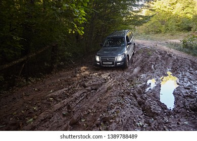 Karachay-Cherkessia, Russia - Oktober 2017: Mitsubishi Pajero car rides a muddy road with puddles against the background of the forest. off-road and active rest