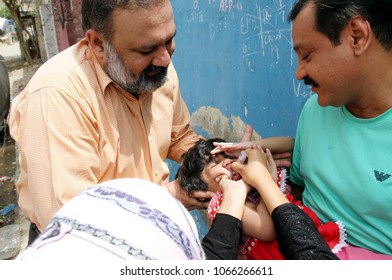 KARACHI, PAKISTAN - APR 10: Union Council (UC-26) Chairman, Qasir Imtiaz  administrating anti polio vaccine to a child during campaign at local compound on April 10, 2018 in Karachi.