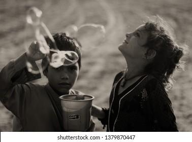 Karachi, Pakistan - April 24, 2019: Street children enjoy blowing bubbles at Clifton Beach in Karachi, Pakistan
