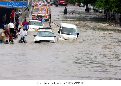 KARACHI, PAKISTAN - AUG 25: Commuters are facing difficulties in transportation due to stagnant rainwater after overflow of rain drain caused by heavy downpour on August 25, 2020 in Karachi.