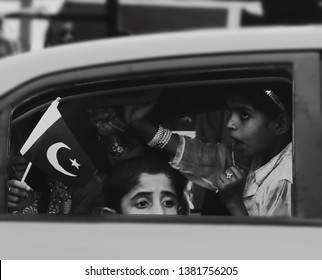 Karachi, Pakistan - August 14, 2018: Unidentified children celebrate Pakistan's Independence Day squished in the back seat of a car.