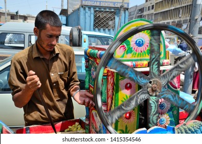 Karachi, Pakistan - August 9, 2016: A Pakistani man in salwar kameez holds a long knife while tending to his colorfully painted sugar cane juice machine outside the city's iconic Empress Market.