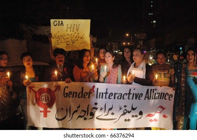 KARACHI, PAKISTAN - DEC 01: Members of Gender Interactive Alliance Welfare for Eunuchs hold lightened candles during a demonstration on occasion of the World AIDS Day on December 01, 2010 in Karachi, Pakistan.