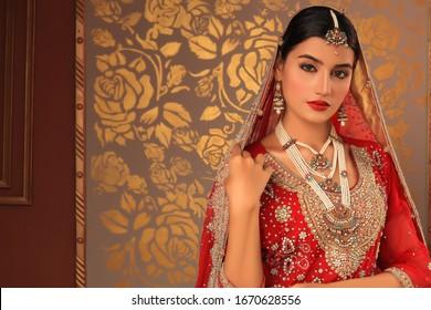 Karachi, Pakistan - February 10, 2020: Beautiful lady in Indian bridal red dress. traditional lehnga wedding dress