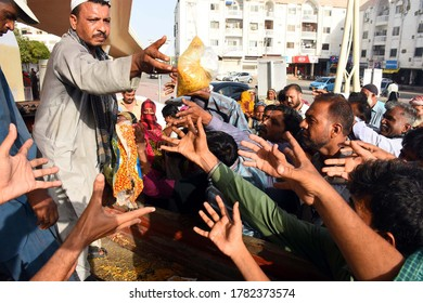 KARACHI, PAKISTAN - JUL 23: People are collecting food packets without any safety measures and social distancing that may cause spread of the coronavirus (COVID-19)  on July 23, 2020 in Karachi.