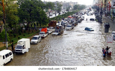 KARACHI, PAKISTAN - JUL 27: People and commuters are facing difficulties in transportation on flooded road due to poor sewerage system, after heavy downpour of monsoon on July 27, 2020 in Karachi