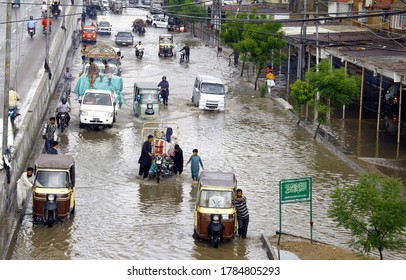 KARACHI, PAKISTAN - JUL 27: People and commuters are facing difficulties in ransportation on flooded road due to poor sewerage system, after heavy downpour of monsoon on July 27, 2020 in Karachi.