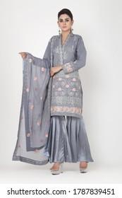 Karachi, Pakistan: July 30, 2020: Beautiful trendy woman in designer dress. posing in studio. Fashion concept.