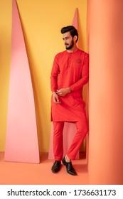 Karachi, Pakistan - May 02, 2020: Pakistani man in traditional wear OR kurta / pyjama cloths. Male fashion model in sherwani, posing in studio round, wedding Fashion concept