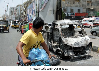 KARACHI, PAKISTAN - MAY 08: Commuters look wreckage of brunt vehicles that were burn in clash between two political parties on last night, at University road on May 08, 2018 in Karachi.