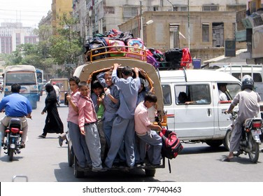 KARACHI, PAKISTAN - MAY 24: Schoolchildren dangerously travel on vehicle and put their lifes in danger as they are going to their homes after school at Saddar area on May 24, 2011in Karachi, Pakistan